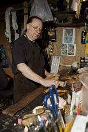 Leather crafter Chip Lorimer dyes a belt in his workshop.
